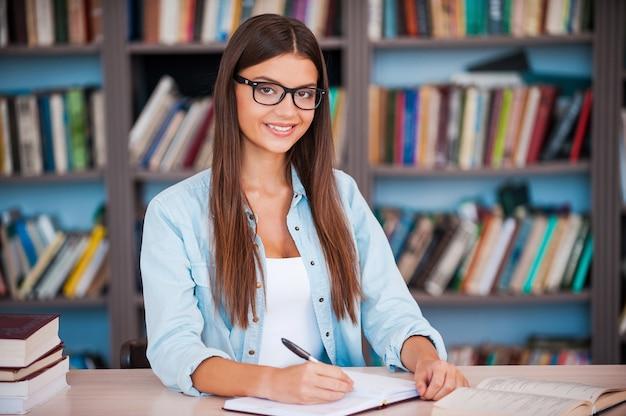 학생이 되어서 너무 행복합니다! 아름다운 젊은 여성이 메모장에 무언가를 쓰고 도서관 책상에 앉아 카메라를 바라보고 있다