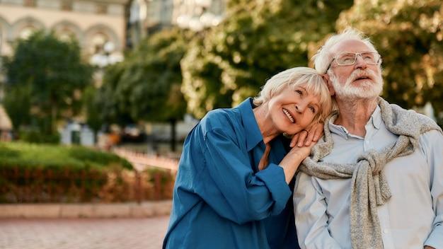 남편의 어깨에 기대고 웃고 있는 아름다운 노년 여성의 행복한 함께 초상화