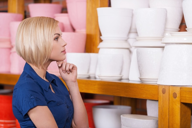 So hard to choose! beautiful young blond hair woman holding hand on chin and looking at the shelf with multi-colored flower pots