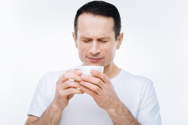 So hot. pleasant nice handsome man holding a cup and blowing at his coffee while wanting to drink it