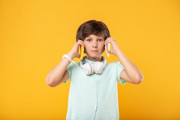 興味深い。 2つの電話を持ち、ヘッドフォンを身に着けている驚いたハンサムな男の子