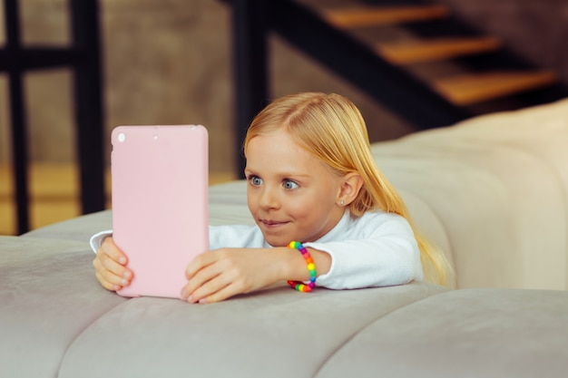 So interesting. attentive girl expressing positivity while looking at screen of her gadget