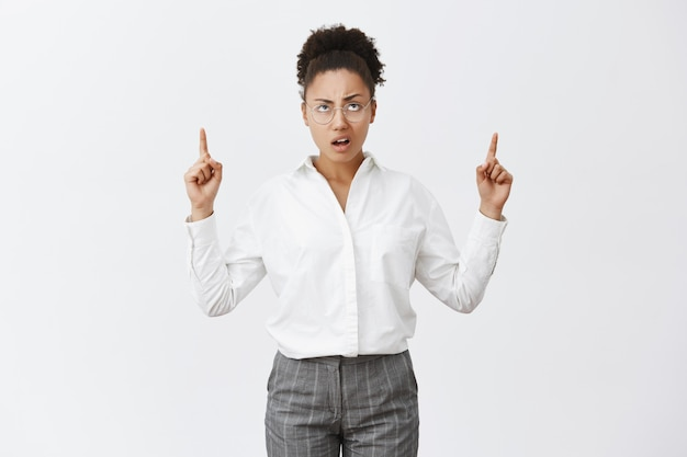 So lame. portrait of unimpressed displeased and disappointed african-american female entrepreneur in glasses and pants, frowning, pointing and staring questioned up with doubtufl and unhappy face