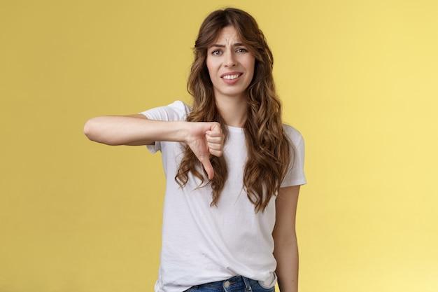 だからあなたは敗者をラメします。無知な卑劣なイケメンの女性は自分の判断を下します否定的な意見は同意しません顔をゆがめたクリンジ嫌い親指を下に向けて失望した印象のない黄色の背景