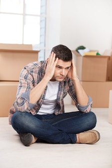 So many boxes to unpack. depressed young man sitting on the floor and holding head in hands while cardboard boxes laying on the background