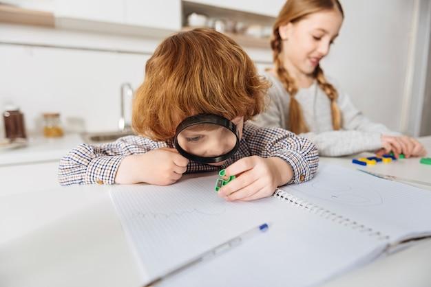 너무 많은 세부 사항. 그의 여동생이 수학 설명을 사용하여 다채로운 플라스틱 숫자 중 하나를보고 큰 렌즈를 사용하여 집중된 활기찬 생강 소년