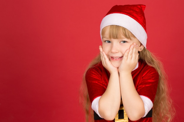 많은 선물이 올 것입니다. 흥분하고 유쾌하게 웃는 그녀의 손에 그녀의 얼굴을 받아 넣는 크리스마스 복장을 입고 어린 소녀의 스튜디오 샷