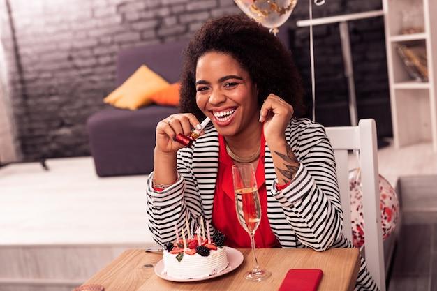 Так весело. радостная милая женщина сидит перед тортом, наслаждаясь вечеринкой по случаю дня рождения