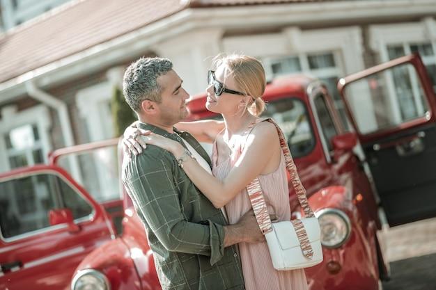 너무 많은 사랑. 열린 복고풍 자동차 앞에 서 있는 아름다운 부부가 서로 껴안고 있습니다.