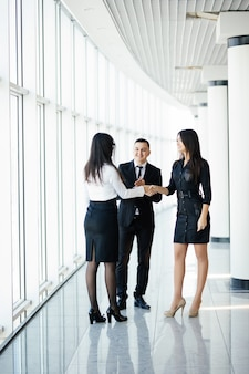 So nice to meet you. young beautiful women shaking hands with smile while standing at the office