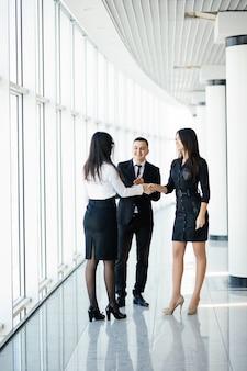 만나서 정말 반갑습니다. 사무실에 서있는 동안 미소로 악수하는 젊은 아름다운 여성