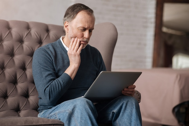 So painful. portrait of elderly handsome man with strong toothache while sitting on sofa and using laptop at home.