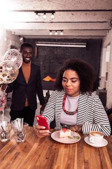 Так приятно. позитивная милая женщина, держащая свой смартфон, читая для нее поздравления с днем рождения