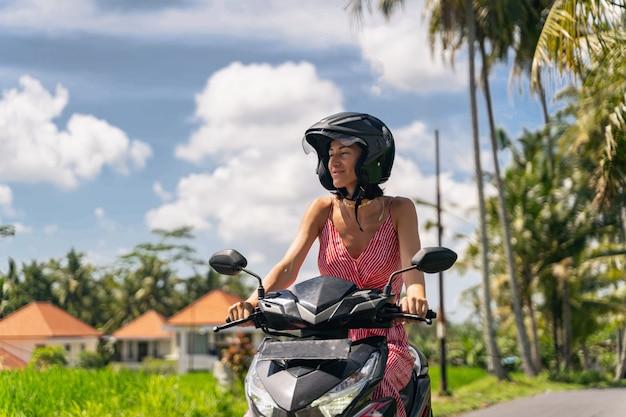 매우 기쁘게 생각합니다. 오토바이를 타는 동안 얼굴에 미소를 유지하는 매력적인 젊은 여성