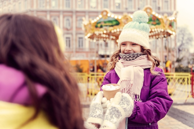 So pleased. delighted girl expressing positivity while walking in amusement park