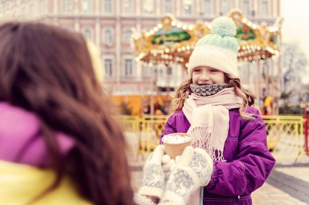 너무 기뻐요. 놀이 공원에서 걷는 동안 긍정적 인 표현을 기쁘게 생각하는 소녀