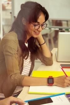 Такой застенчивый. довольно молодая женщина с удовольствием улыбается во время учебы