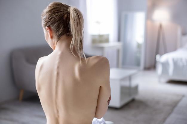 Такой тонкий. симпатичная молодая модель показывает свою спину, страдая от анорексии