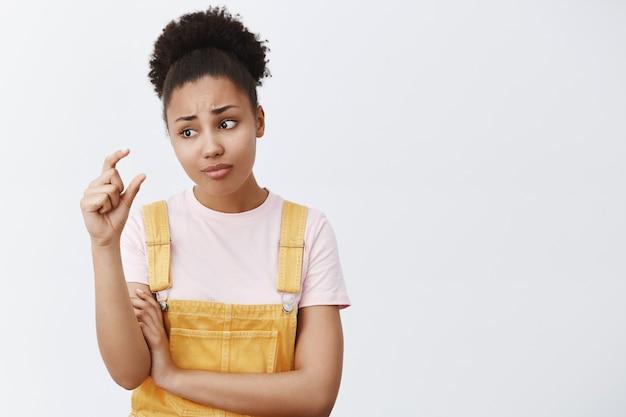 Так мало, что стыдно. портрет недовольной расстроенной и невпечатленной студентки афроамериканского происхождения в модном желтом комбинезоне, хмурящейся, глядя на пальцы, формирующей что-то маленькое и крошечное