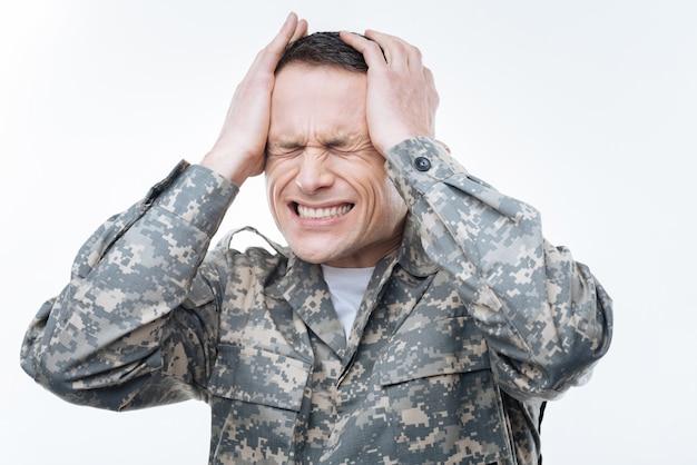Так напрягся. несчастный унылый военный, закрывая глаза и держась за голову во время стресса
