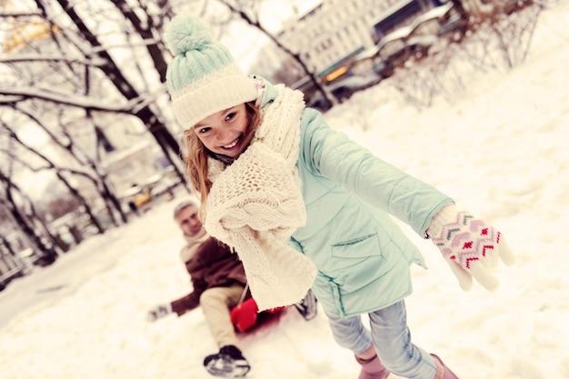 매우 강하다. 전경에 서있는 동안 그녀의 얼굴에 미소를 유지하는 즐거운 아이