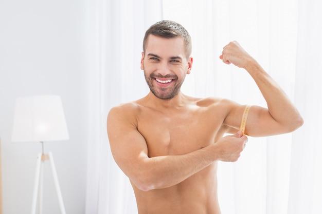 とても強い。あなたに彼の筋肉を見せながら笑っている素敵なしっかりした男