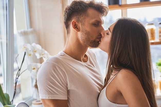 So sweet. charming longhaired girl standing in semi position and kissing her boyfriend with pleasure