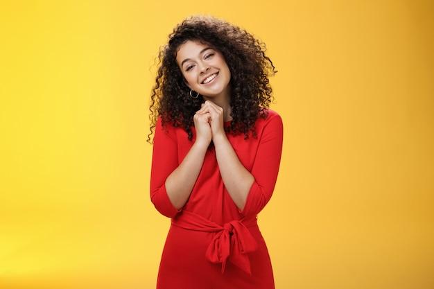 とても甘いあなたを愛しています。赤いドレスを着た柔らかくてばかげたかわいい縮れ毛の若い女性の肖像画は、顔の近くで手をつないで、告白の心温まる瞬間に触れて笑顔で頭を傾けます。