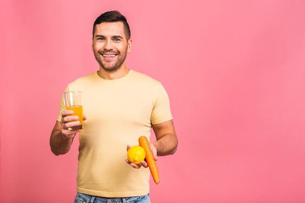 너무 맛있고 건강한 다이어트 개념. 오렌지 해독 음료, 과일 및 야채와 함께 유리를 들고 매력적인 젊은 남자