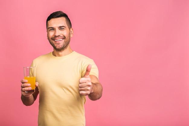 너무 맛있고 건강한 다이어트 개념. 오렌지 해독 주스 음료와 함께 유리를 들고 매력적인 젊은 남자