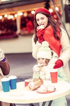 정말 맛있어. 그녀의 가족과 함께 시간을 보내는 동안 과자를 먹는 매력적인 소녀