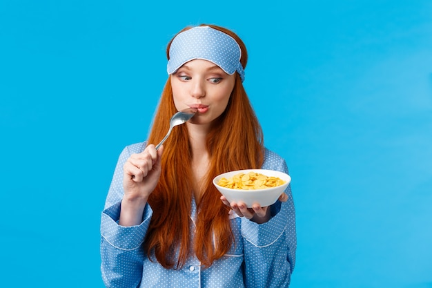 So tasty. cute and tender feminine girl starting day with healthy diet, eating delicious cereals, licking spoon and staring plate tempting and eager eat it, standing blue wall
