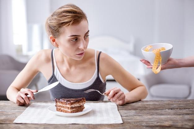Так вкусно. милая молодая женщина ест торт, упрекая себя за это