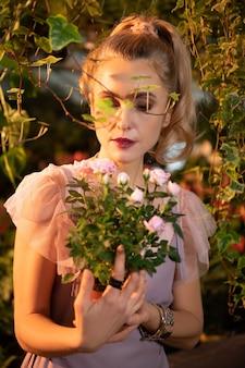 とても優しい。フラワー ガーデンにいる間、美しいバラを見ている素敵な若い女性