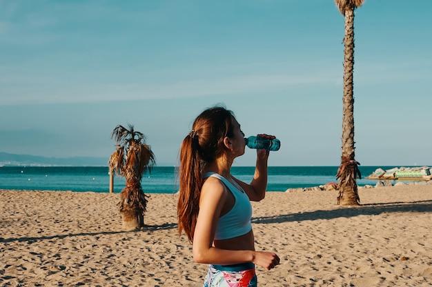 のどが渇いています。屋外で運動しながら水を飲むスポーツ服の美しい若い女性
