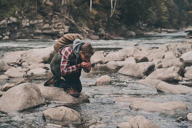 너무 목말라! 산에서 하이킹하는 동안 강에서 물을 마시는 잘 생긴 젊은 현대 남자