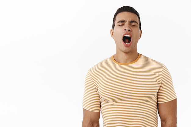 So tired. attractive young masculine male in striped t-shirt