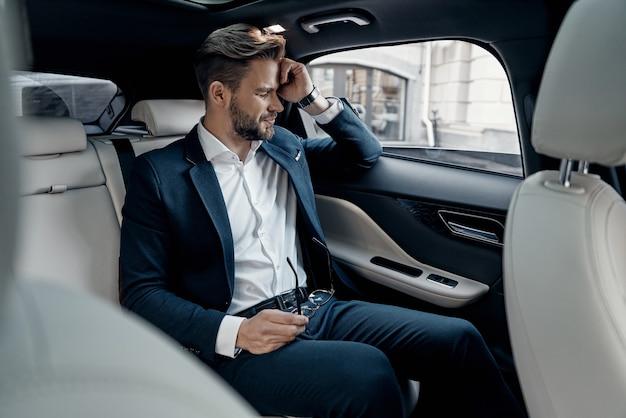 너무 피곤해. 차에 앉아있는 동안 눈을 감고있는 formalwear에서 좌절 된 젊은 남자