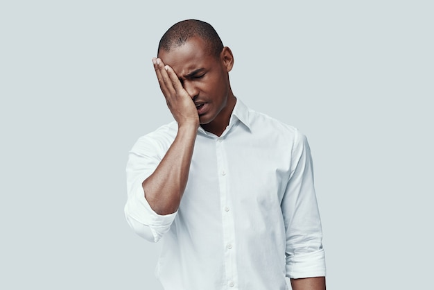 So tired. young african man making a face while standing against grey background