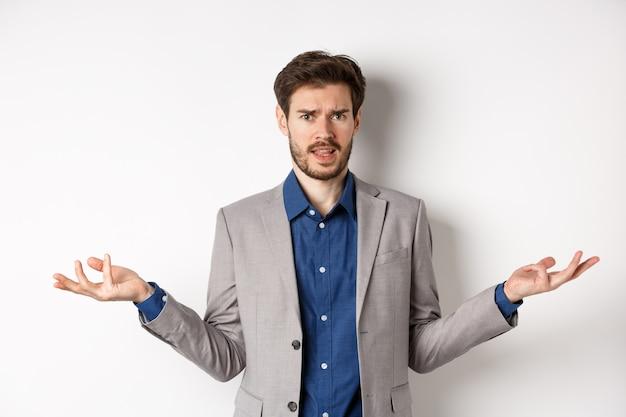 Так что за дело. смущенный и раздраженный бизнесмен развел руками в сторону и недоуменно хмурясь, не может понять, что не так, стоя на белом фоне.