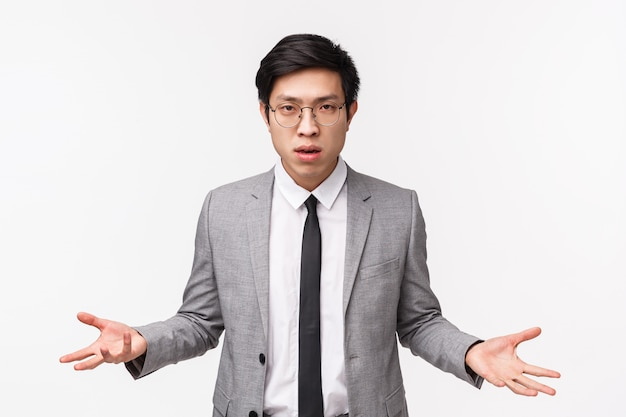 So what. waist-up portrait of annoyed and skeptical, unimpressed serious-looking asian businessman spread hands sideways with dismay, puzzled cant understand what person wants