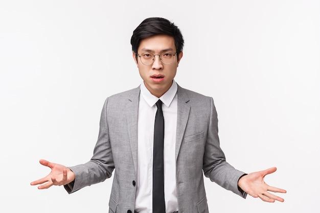 그래서 뭐. 짜증과 회의, 인상적인 심각한 찾고 아시아 사업가의 허리 업 초상화는 실망으로 옆으로 손을 확산, 의아해 사람이 원하는 것을 이해할 수 없음