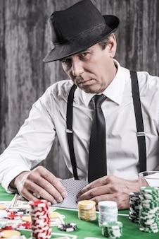그래서 무엇을 얻었습니까? 셔츠와 멜빵을 입은 진지한 노인이 포커 테이블에 앉아 주위에 돈과 도박 칩이 든 카드를 들고 있습니다.
