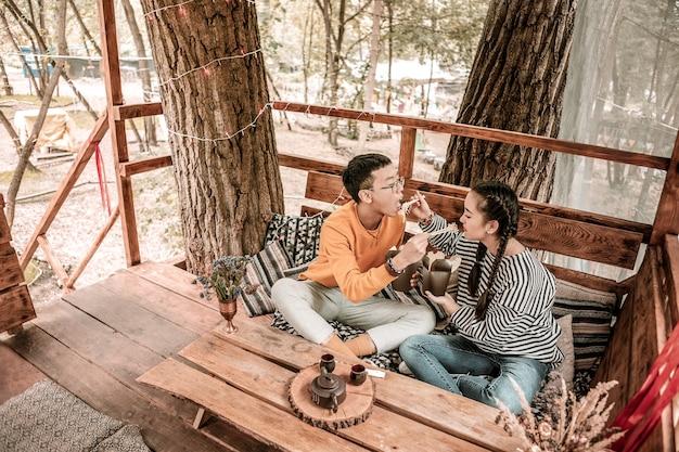 とてもおいしいです。野外ディナーを楽しみながら向かい合って座っている遊び心のある人 Premium写真