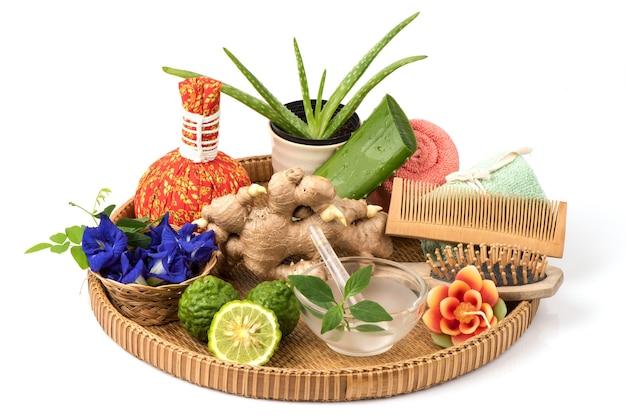アロエベラ、リナカンツスナス、バタフライエンドウ豆の花、カフィアライム、生姜を白い背景に分離して髪を浸します。