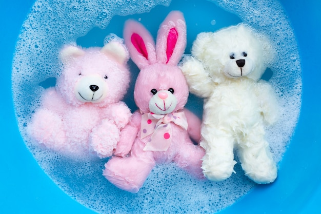 Soak rabbit doll with  toy bears in laundry detergent water