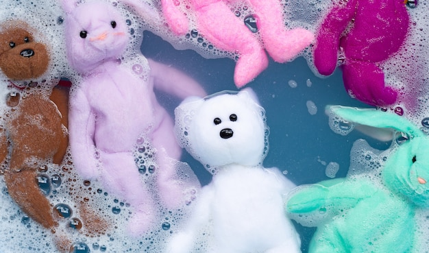 Soak rabbit doll with  toy teddy bear in laundry detergent water dissolution before washing.  laundry concept