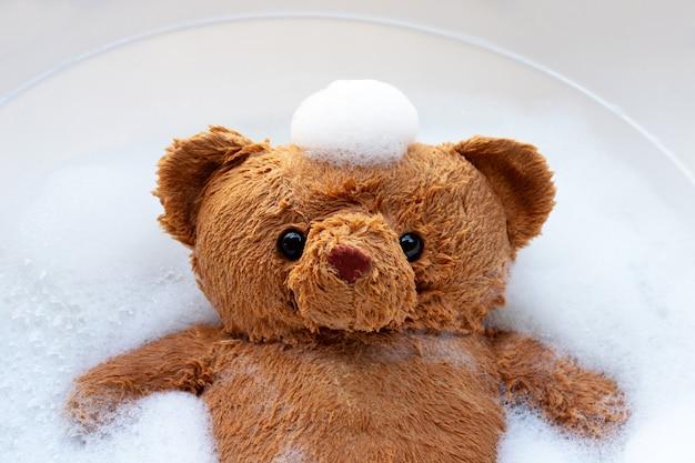 세탁하기 전에 세제 물 용해에 장난감 곰을 담그십시오