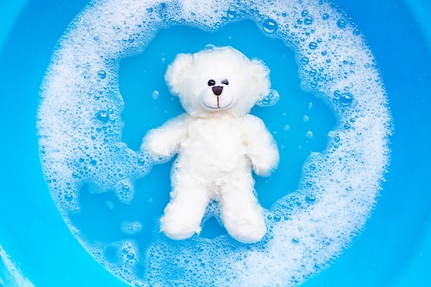 Soak toy bear in laundry detergent water dissolution before washing.  laundry ,