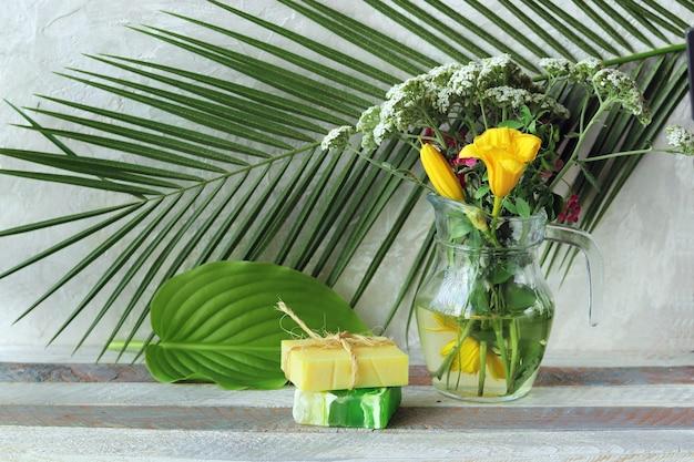 石鹸、木製のテーブルにアロマオイルと薬草とガラス瓶の花束